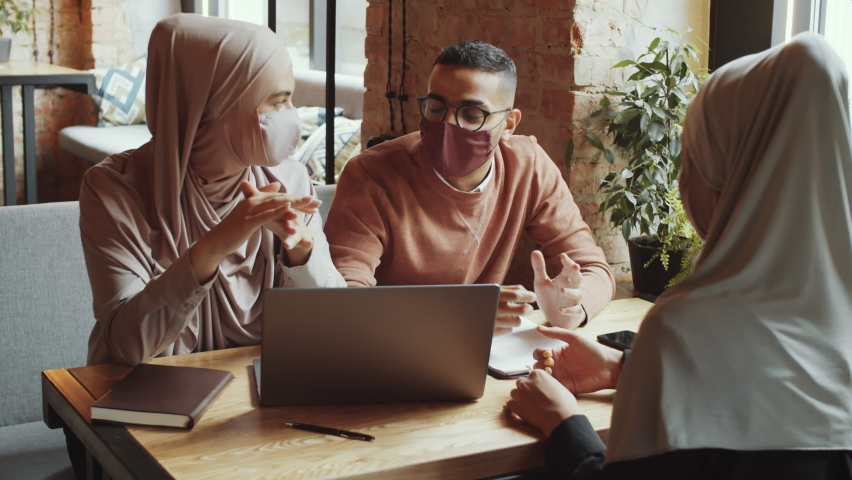 Two muslim women and middle eastern man in face masks speaking about business at cafe table while meeting together on lunch during covid-19 outbreak Royalty-Free Stock Footage #1059994184