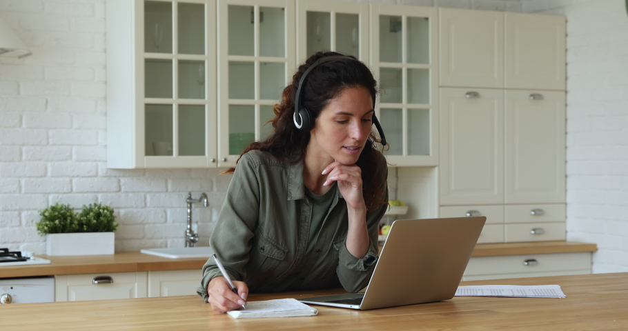 35s woman learn language looks at laptop writes notes on copybook listens audio course through wireless headset learning english in home kitchen alone. Self-education, knowledge improvement concept