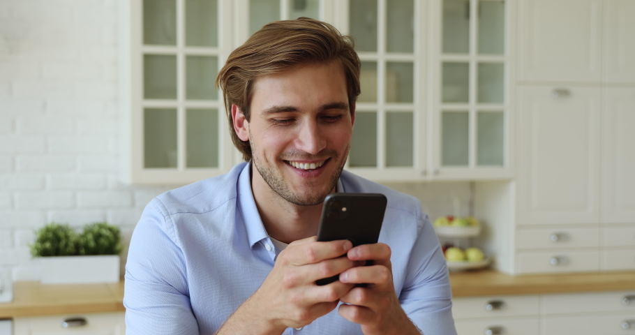 Guy hold in hands smartphone smiling enjoy remote online communication with girlfriend, share photos, chatting in social media networks, make food order easy comfort wireless modern tech usage concept