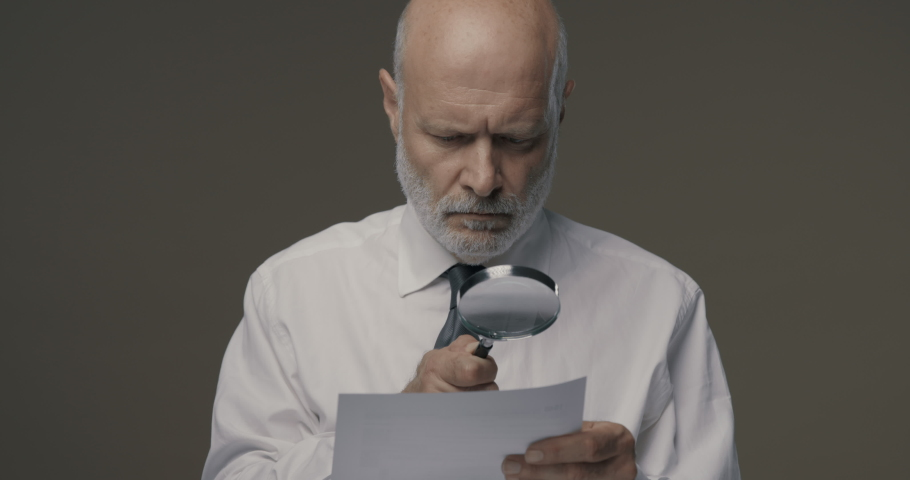 Businessman checking a document using a magnifier, contracts and agreements concept Royalty-Free Stock Footage #1060016531