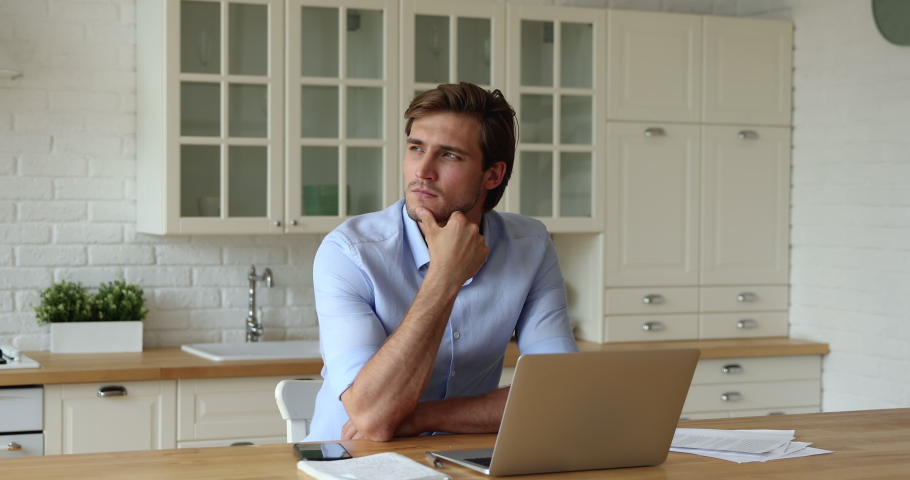 Business man sit at table in kitchen near laptop touches chin thinks over strategy work remotely from home, creative job, generating new fresh ideas, searching solution. Doubts and challenges concept | Shutterstock HD Video #1060020125