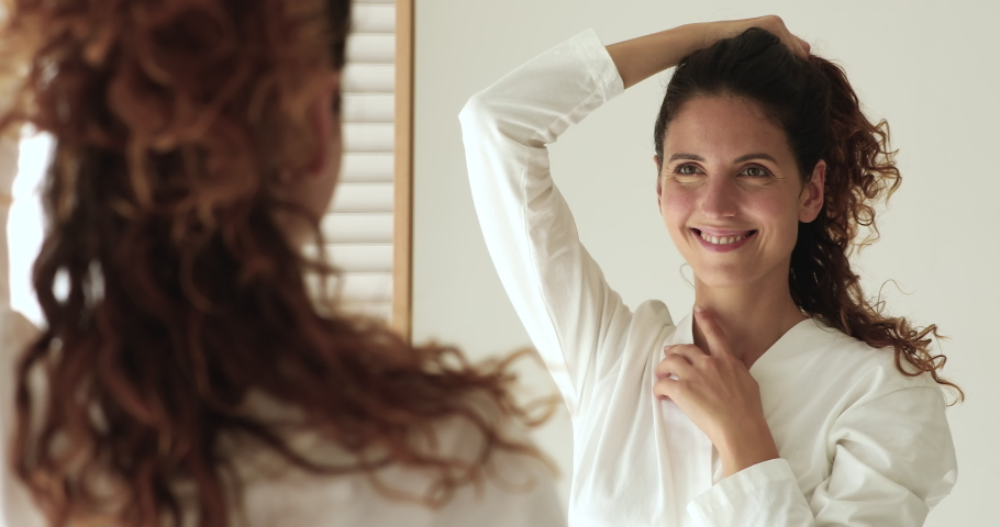 Close up 30s woman in bathrobe freshen up herself in morning looking reflected in mirror touching healthy strong brown curly hairs feels happy. Haircare and styling, best hair products usage concept Royalty-Free Stock Footage #1060020185