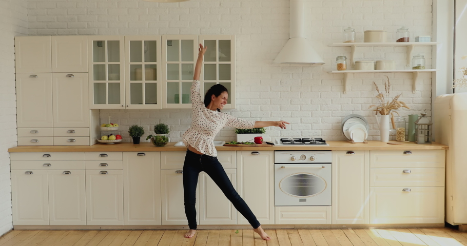 Wide full-length wide view in modern spacious kitchen lively housewife singing feels happy, dancing barefoot on warm floor with underfloor heating system. Hobby and luxury home owner free time concept Royalty-Free Stock Footage #1060022390