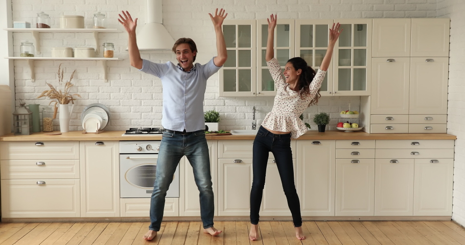 Full length couple dancing together in cozy spacious domestic kitchen while listen energetic music feels cheerful. Dating and relationships, happy home owners celebrate relocation at new house concept Royalty-Free Stock Footage #1060022423
