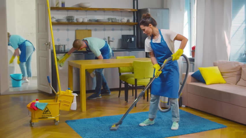 Professional team of janitors vacuum cleaning carpet, wiping furniture and washing bathroom. Home cleaning service crew working in modern loft apartment