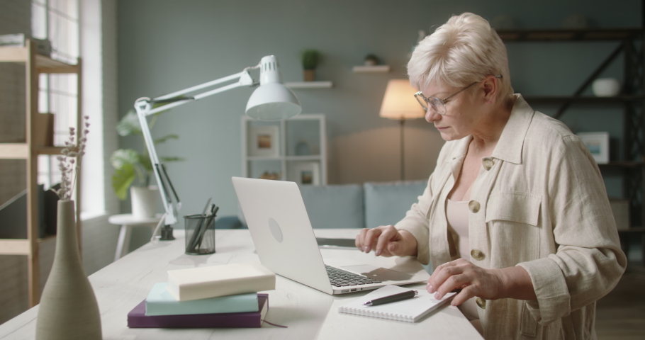 Mature caucasian lady in 50s is working on her laptop computer at home, typing on keyboard. Experienced manager is doing her project during self isolation 4k footage Royalty-Free Stock Footage #1060036127