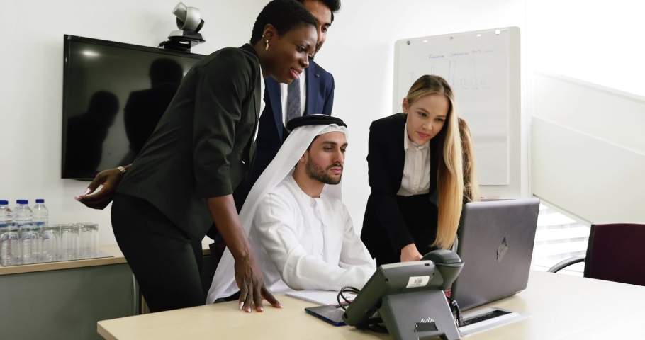 Mixed business team in Dubai. Business meeting with men wearing kandura and western people in the office | Shutterstock HD Video #1060041494