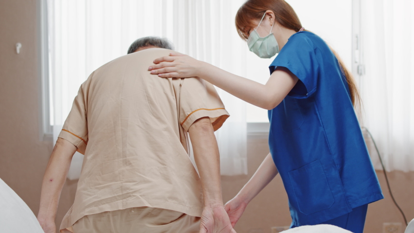 Female Asian nurse support senior male patient stand up and walk from bed in hospital. Nursing home, medical service, physiotherapy, hospitality, or recovery treatment concept Royalty-Free Stock Footage #1060044530