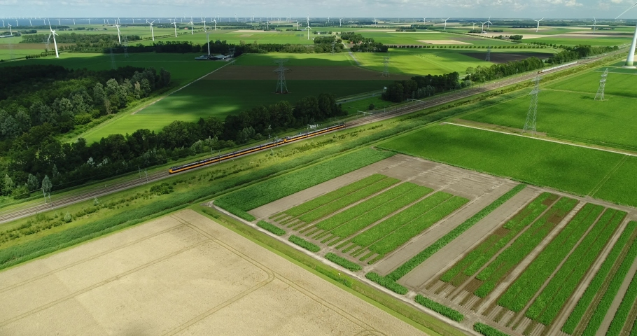 4k aerial horizon view of intercity train passing on railway surrounded by green landscape farmland and electricity pylons with energy generating wind turbines, Flevoland in the Netherlands Royalty-Free Stock Footage #1060045163
