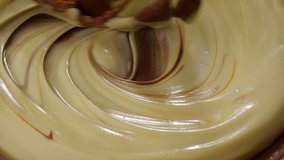 Mixing hazelnut chocolate cream. Mixing melted liquid milk chocolate with a whisk.