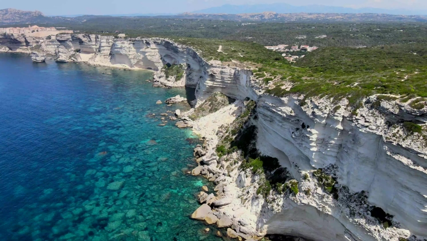 Shooting from the drone of the immense white cliff on the turquoise sea near Bonifacio Corsica