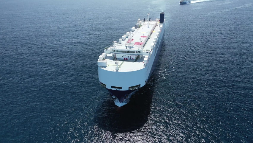 Aerial drone video of huge car carrier ship RO-RO (Roll on Roll off) cruising in Mediterranean deep blue Aegean sea Royalty-Free Stock Footage #1060063994
