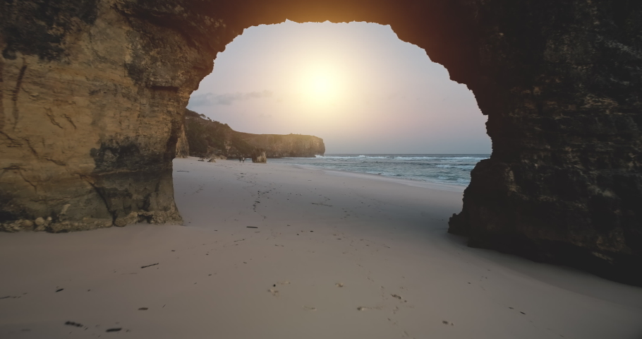 Giant hole of cliff wall drone flight to sand beach at ocean bay with walking tourists aerial view. Indonesia sea waves washed sandy and rocky coast at sun shine summer day. Cinematic soft light shot