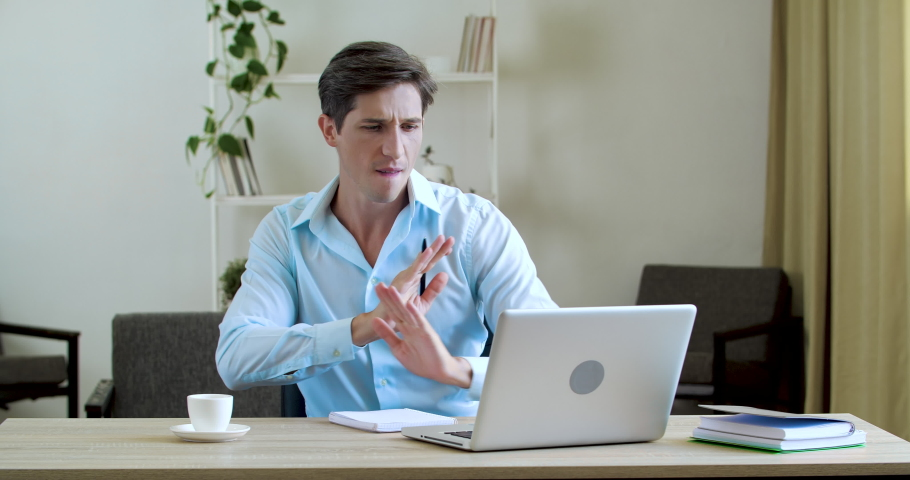 Portrait of happy businessman sitting in office or at home at table, working at laptop online, reading positive news, celebrating, dancing with joy, actively moving his hands, drinking aromatic coffee Royalty-Free Stock Footage #1060073960