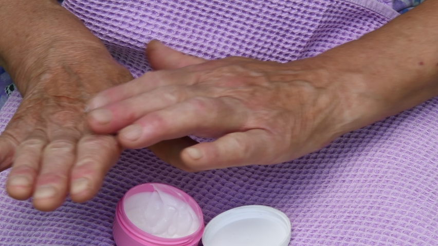 Female hands of senior woman open small circle jar and apply white cream over her wrinkled skin of hand palm. Elderly skin care treatment concept Royalty-Free Stock Footage #1060083200
