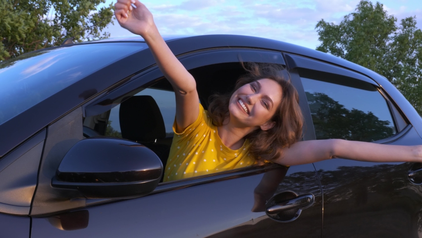 Happy woman with key sitting in new car
