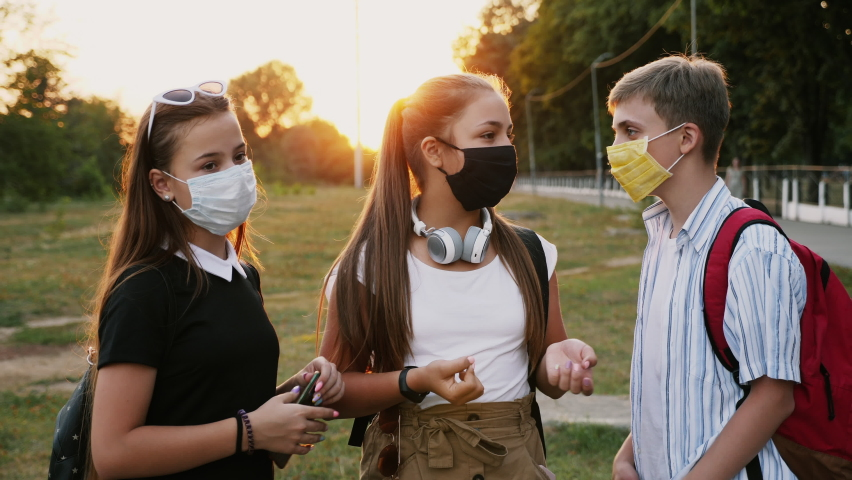 Three teenage schoolchildren with protective masks on their faces talking to each other on the street Royalty-Free Stock Footage #1060089935