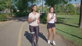 Two young cute women caucasian and hispanic jogging at the park to keep fit - Couple of female mixed race friends running together in the morning for their healthy