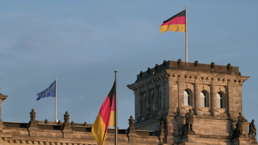 Close shot of German and EU flags flying in strong wind on the German Reichstag #1060095239
