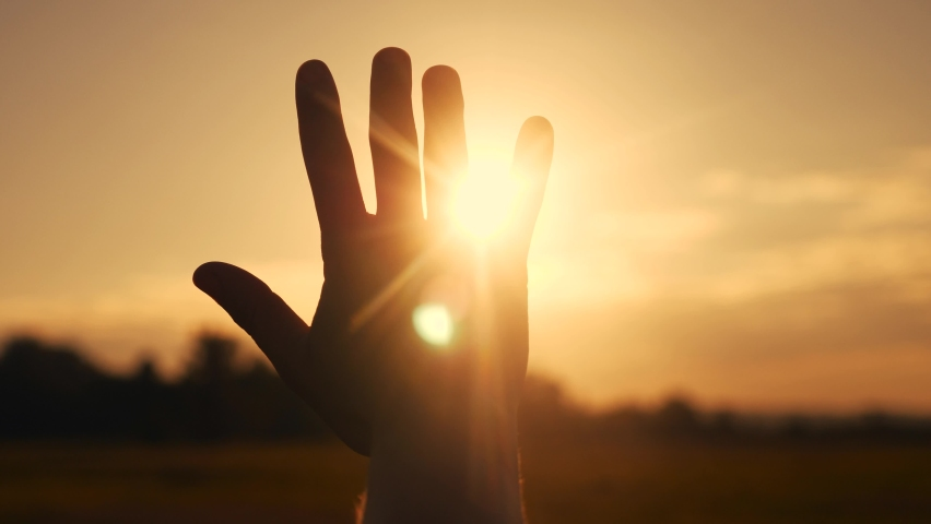 girl stretches out her hand in the sun. faith in god dream a religion concept. hand in the sun close-up silhouette sunlight dream of happiness Royalty-Free Stock Footage #1060095611