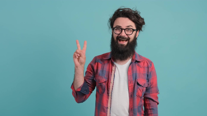 Close up of a funny bearded man showing victory symbol with fingers isolated over turquoise background. | Shutterstock HD Video #1060100858