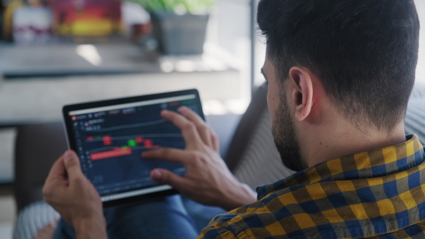 Young adult man lying down on couch in living room at home, people trading on line with tablet pc connected to stock market. People, finance, investments. Over the shoulders Royalty-Free Stock Footage #1060103882