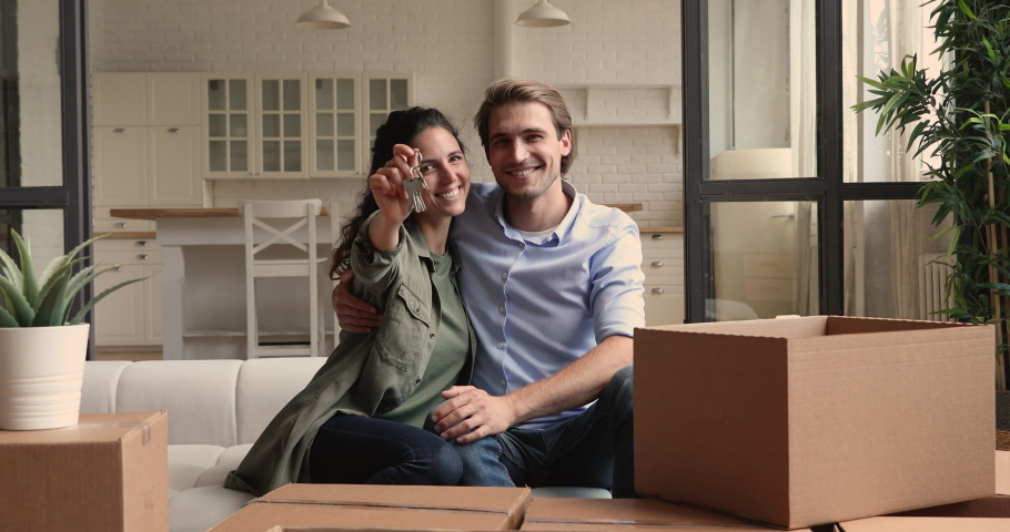 Happy young couple sit on sofa near of heap belongings in cardboard boxes, wife showing to camera bunch of keys, symbol of new modern home. Excited homeowners portrait, real estate and tenancy concept Royalty-Free Stock Footage #1060104272