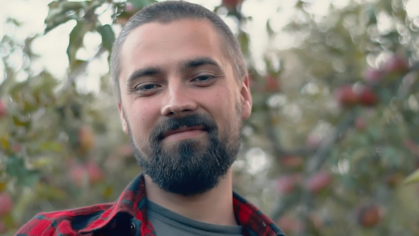 Portrait of a smiling bearded caucasian gardener against the background of trees with apples. Organic farm concept. Close-up, slow motion | Shutterstock HD Video #1060110797
