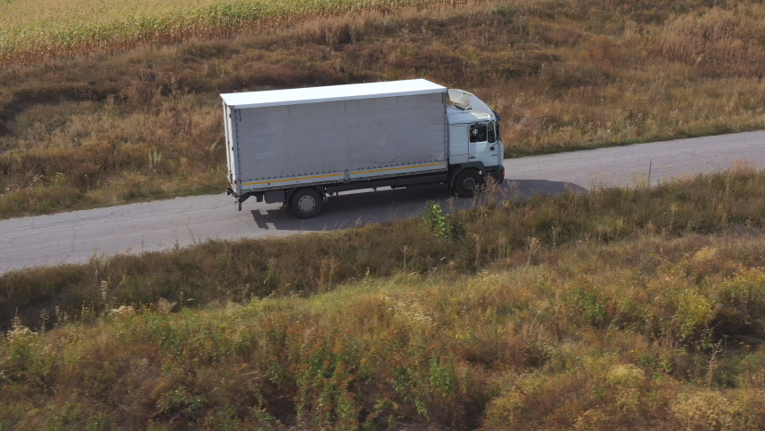 Aerial shot of truck with cargo trailer driving on road and transporting goods. Flying over delivery lorry moving along highway passing near fields in countryside. Scenic nature scene. Side view Royalty-Free Stock Footage #1060114553