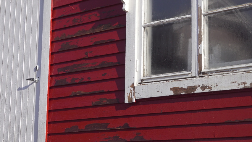 Close up video on Power washing loose paint with high pressure water blowing red color paint away from small wooden red house. Summer cabin renovation, countryside, high pressure wash.