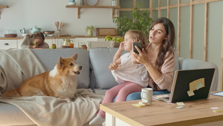 A Busy Mother Trying to Work Remotely With Her Children's at Home. The Daughter Interferes With Her Mother's Work. A Little Daughter Don't Want to Sits on the Lap of Her Mother. Mother Begin Annoyed. #1060128650