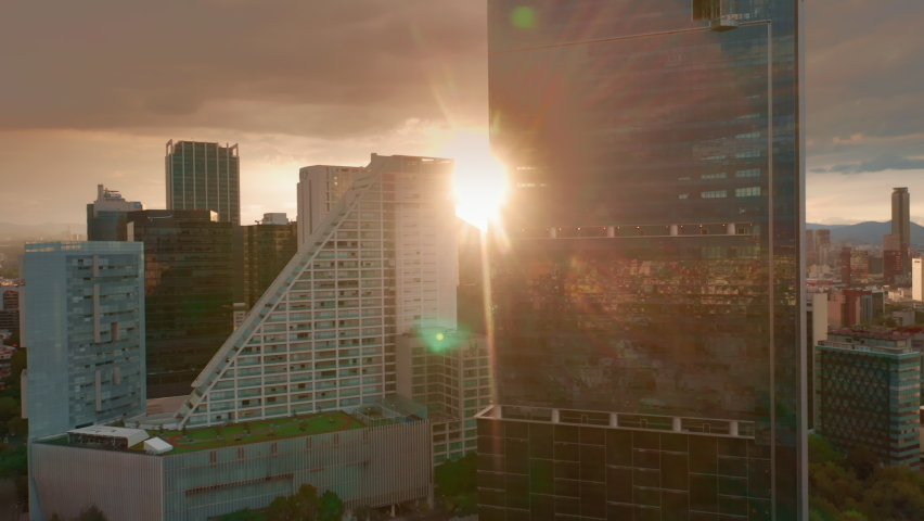 Cinematic view on sunset light and golden clouds over the modern business area in Mexico city. 4K aerial of glass buildings architecture with latin cityscape on motion background. Business offices Royalty-Free Stock Footage #1060137059