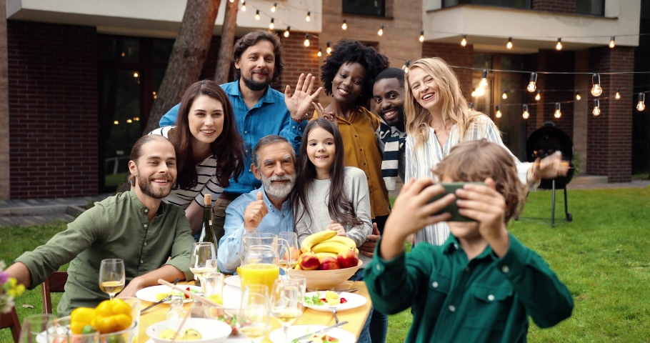 Mixed-races happy family at party dinner outdoor in yard smiling and posing to smartphone camera while small boy taking selfie photo. Multi ethnic people making photos together at barbeque Celebration