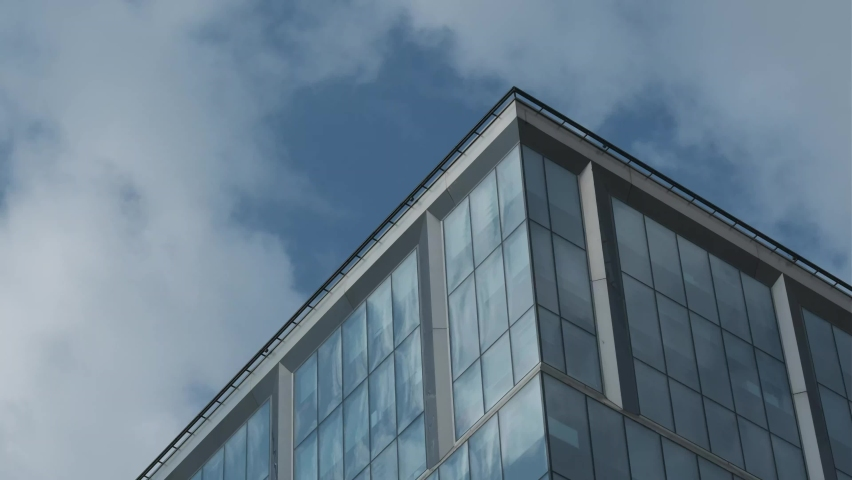Close up view, white clouds passing by and reflecting in the windows of the building in Moscow, Russia Royalty-Free Stock Footage #1060151519