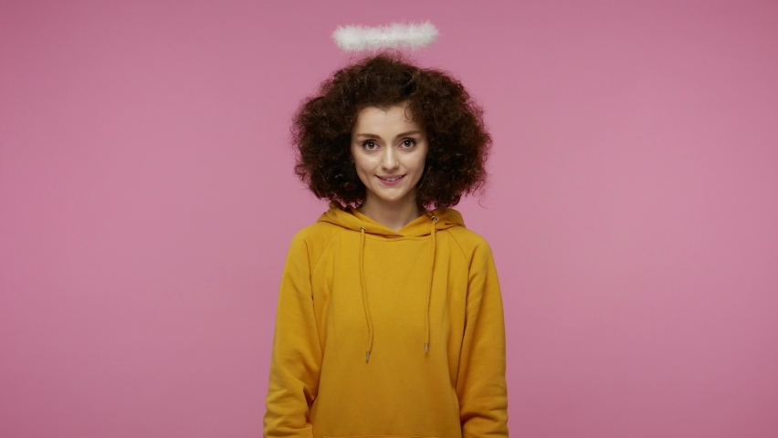 Happy Valentine's Day! Angelic young woman afro hairstyle with nimbus holding pink heart, looking playful flirting and sending air kiss, demonstrating love care, romantic feelings. indoor isolated | Shutterstock HD Video #1060152473