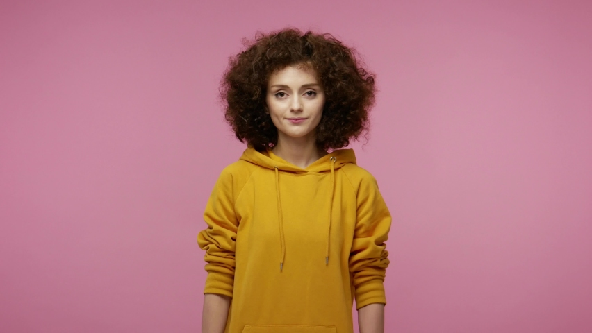 Cheerful trendy young woman afro hairstyle in hoodie showing hashtag gesture, tagging viral web content, famous idea on internet resources, social network. indoor isolated on pink background | Shutterstock HD Video #1060152479