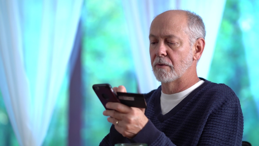 Closeup of mature man using credit card to make purchase on smartphone online, typing in account number, with glass of wine. Royalty-Free Stock Footage #1060153457