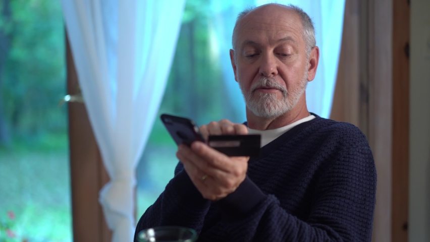 Turning closeup of mature man using credit card to make purchase on smartphone online, typing in account number, with glass of wine. Royalty-Free Stock Footage #1060153463