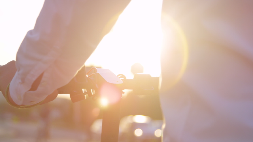 SLOW MOTION, LENS FLARE, CLOSE UP, DOF: Businessman commuting on his electric scooter waits at a stop light. Man in a white shirt holds the handlebar of his e-scooter while waiting at a red light. Royalty-Free Stock Footage #1060160549