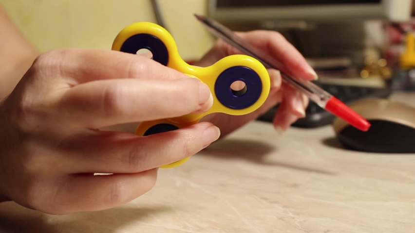 Close-up of yellow hand spinner in hand. A woman's hand twirls a fidget spinner at a computer table. Selective shot. Royalty-Free Stock Footage #1060165298