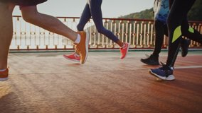 Group of young people practicing morning jog workout on sports path in morning, close up of legs, slow motion