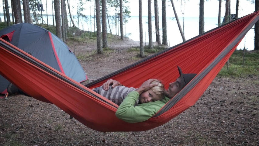 Active family outdoors, travel and adventure with child. Father and son hikers travellers sitting in tourist hammock near camping tent in the forest. Royalty-Free Stock Footage #1060170101