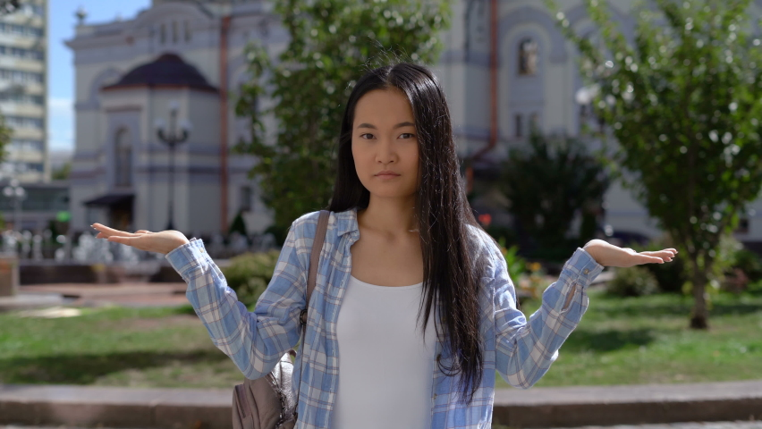 Young Asian woman shows two palms and chooses right or left. 4K Royalty-Free Stock Footage #1060181024