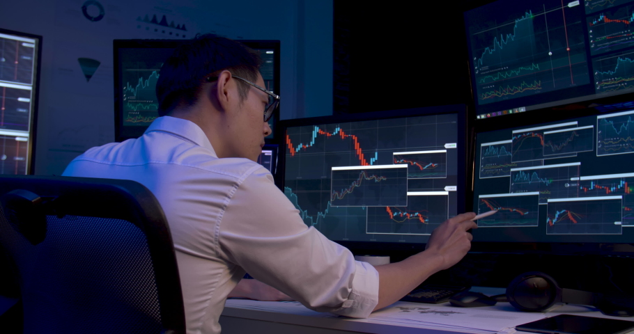 Asian business man is sitting at desk with monitors showing line graphs, charts. Alone male is analyzing stock market trading, strategic planning project of marketing data at late night. Dolly shot. Royalty-Free Stock Footage #1060187531