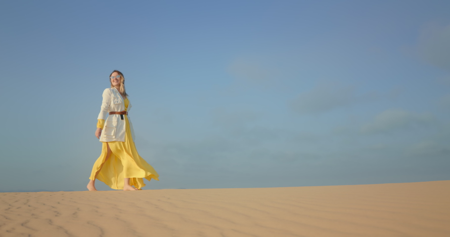 4K slow motion footage with blue space for copy or text on background for commercial usage. Cinematic shot of woman in stylish outfit walking by wavy sand surface. Scenic wild nature landscape view | Shutterstock HD Video #1060189940