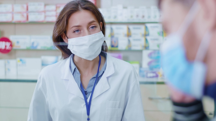Female apothecarist working in drugstore consulting customers. Careful smart woman pharmacist listening to symptoms wearing protective mask selling drugs. | Shutterstock HD Video #1060193747