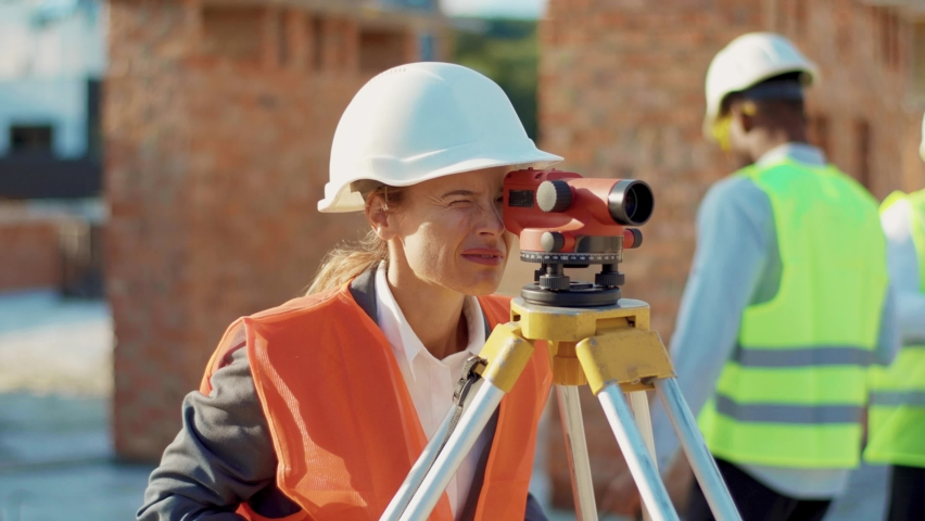 Close up young woman surveyor in work clothes and helmet takes measures with theodolite stand helmet hardhat geodesy digital engineering real estate teamwork infrastructure industry slow motion