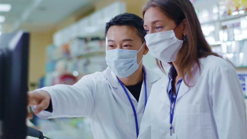 Multi-ethnic couple of pharmacists wearing protective virus masks communicating sharing ideas working together in pharmacy store. Cooperation. Professional people. Royalty-Free Stock Footage #1060194023