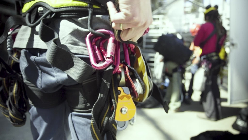 A climbing crew adjusts their harnesses and safety gear before climbing an industrial building. | Shutterstock HD Video #1060201856