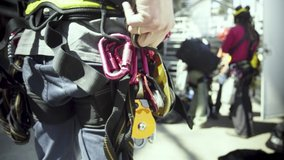A climbing crew adjusts their harnesses and safety gear before climbing an industrial building.